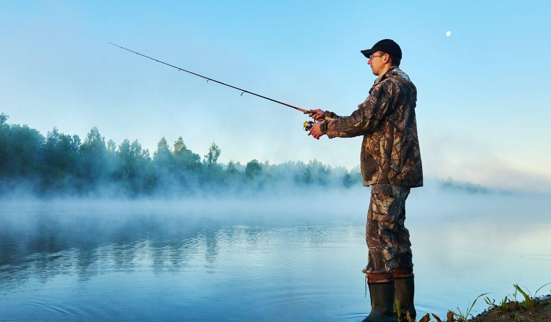 Pescatore sportivo in riva a corso d'acqua